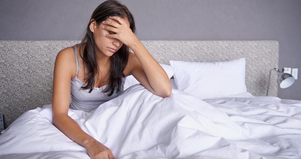 Jovem mulher em sua cama, triste com as mãos sobre o rosto