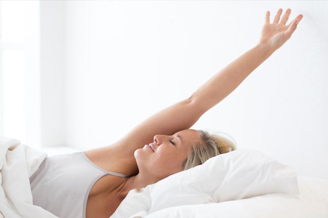 Jovem mulher relaxada com o braço estendido, deitada na cama