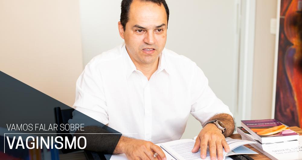 Dr. Max Urologista e Sexólogo, em sua mesa, com as mãos tocando receitas e explicando sobre Vaginismo