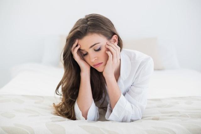 Jovem mulher deitada de bruços na cama, com as mão no rosto, preocupada com a anorgasmia.