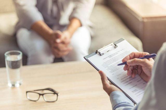 Médico e paciente em consultório, médico preenche ficha com os dados da paciente sobre a anorgasmia.