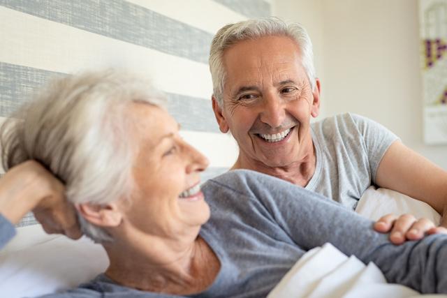 Casal idoso conversando e sorrindo na cama
