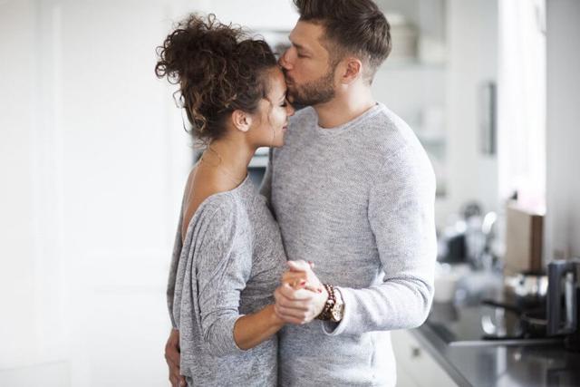 Jovem casal dançando juntos; homem beijando a testa da companheira