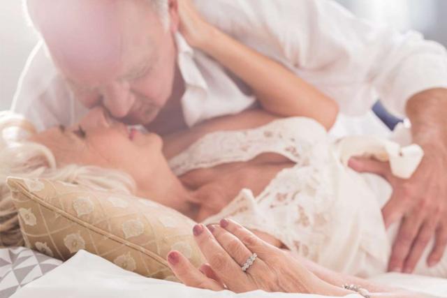Casal idoso beijando-se enquanto deitam na cama e namoram
