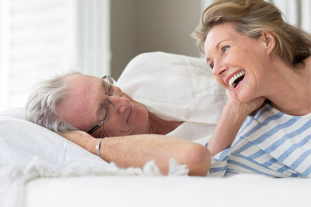 Homem mais velho deitado na cama observando sua parceira mais velha sorrindo