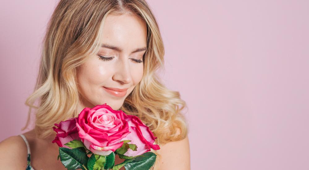 Jovem mulher loira sorrindo ao sentir o perfume do buquê de flores que segura com as mãos