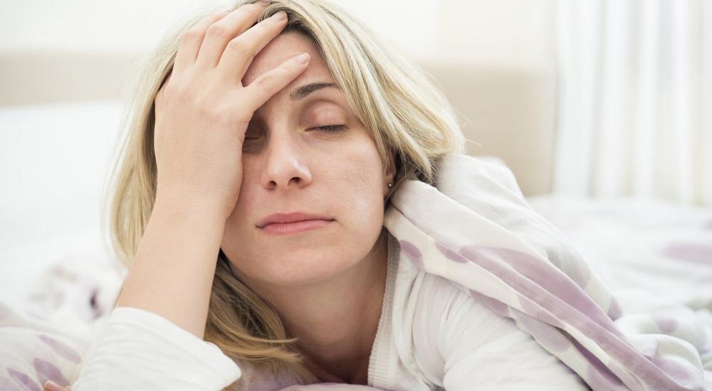 Mulher de meia idade cansada, com os olhos fechados, apoiada sobre uma das mãos no rosto