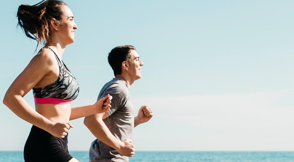 Jovem casal correndo na praia