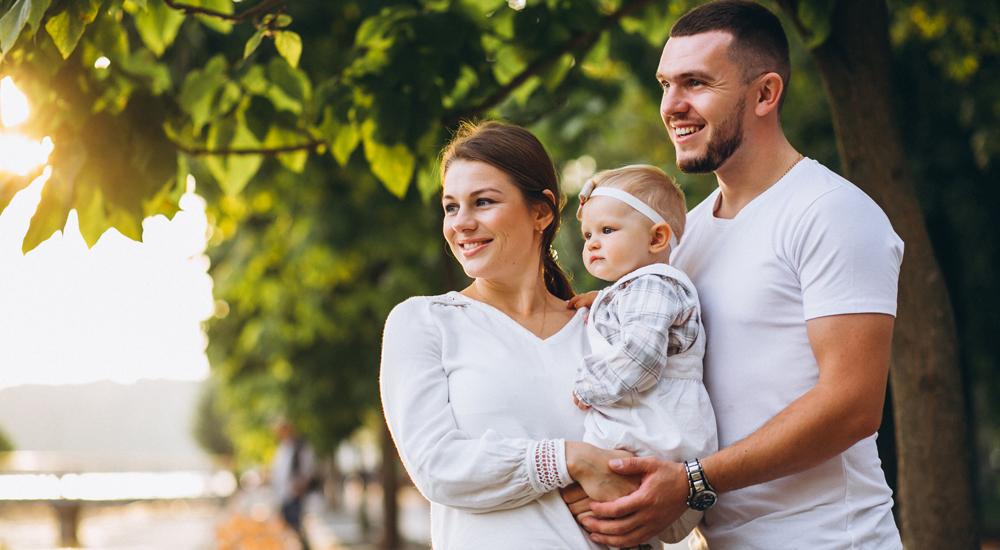 Família feliz e reunida: Mãe carrega bebê no colo enquanto são abraçadas pelo pai.