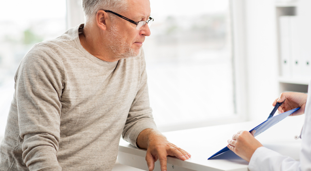 Homem de meia idade conversando com um médico