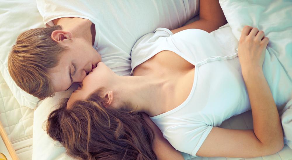 Jovem casal deitado, beijando-se felizes