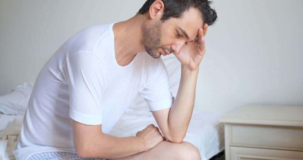 Homem triste sentado a beira da cama com as mãos na cabeça