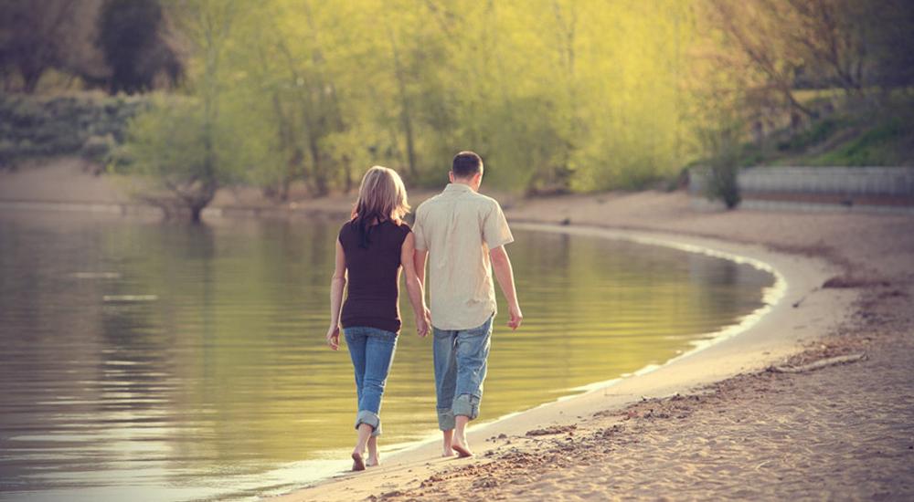 Casal andando junto a beira do lago
