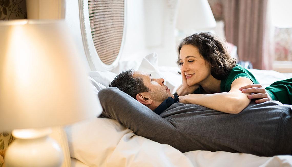 Casal deitado na cama conversando e sorrindo