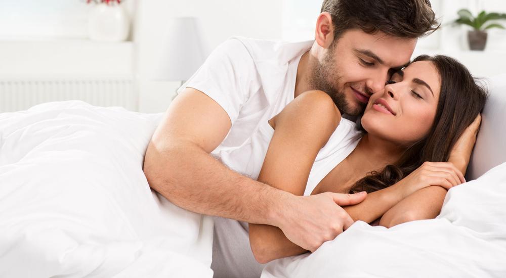 A imagem pode conter um homem e uma mulher, sorrindo e abraçados na cama