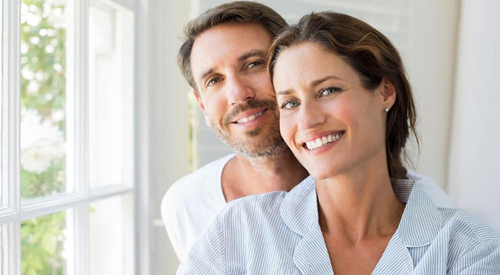 A imagem pode conter um homem e uma mulher abraçados e sorrindo