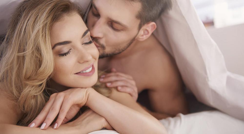 Jovem casal heterossexual feliz, acariciando-se embaixo do edredon