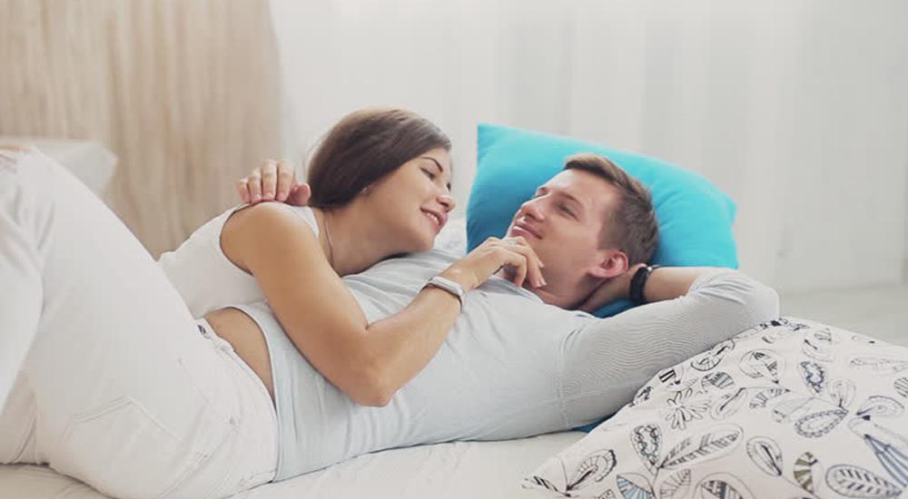 Casal deitado na cama e trocando carícias