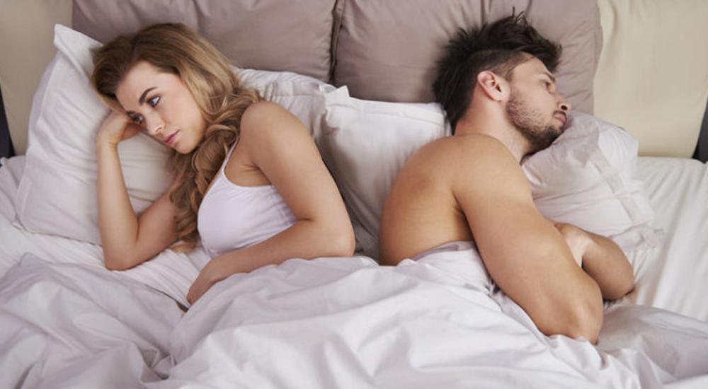 Casal deitado de costas um para o outro